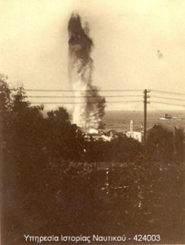 Η στιγμή της έκρηξης μιας εκ των τορπιλών στην προβλήτα του λιμανιού της Τηνου. Η Έλλη διακρίνεται στην δεξιά πλευρά του στύλου.