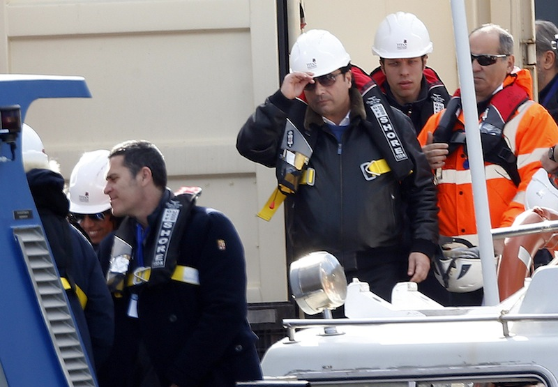 Schettino, the captain of the Costa Concordia, adjusts his helmet as he waits to board the cruise liner at Giglio harbour