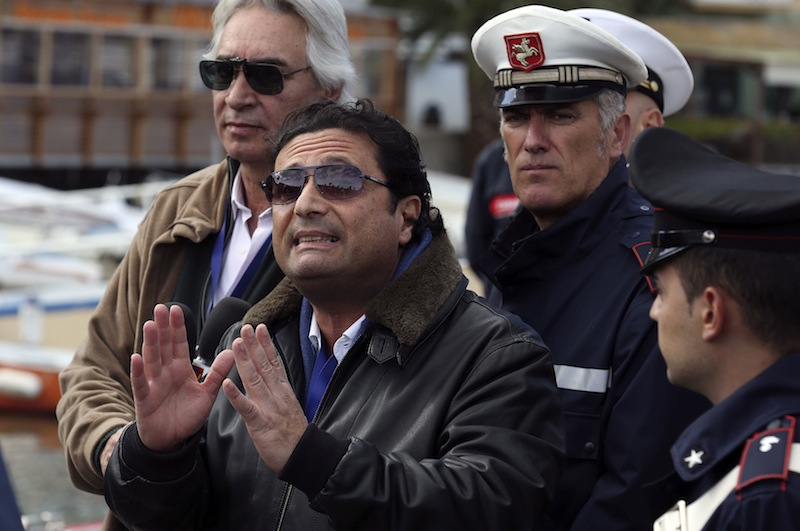 Schettino, the captain of the Costa Concordia, speaks to reporters after going back on board the cruise liner at Giglio harbour
