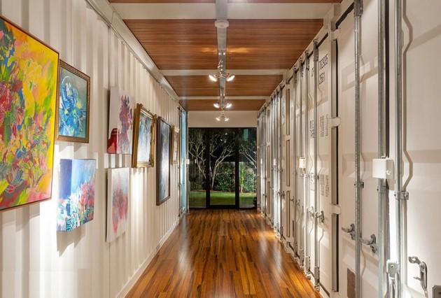 Ένας από τους διαδρόμους του σπιτιού που οδηγεί στον κήπο όπου φαίνονται τα χαρακτηριστικά τοιχώματα ενός κοντέινερ.