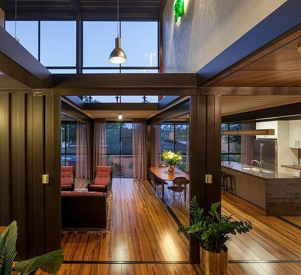 Πατώματα από ξύλο και μεγάλες γυάλινες επιφάνειες συνθέτουν ένα μοντέρνο σπίτι.