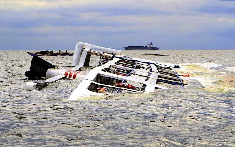 A fishing boat passes the Super Shuttle Ferry 7 which capsized in strong winds and huge waves unleashed by Typhoon Kalmaegi, locally named Luis, in Manila Bay