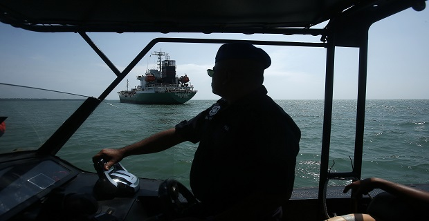 A maritime police approaches the Japanese oil tanker which was raided by armed pirates at Port Klang