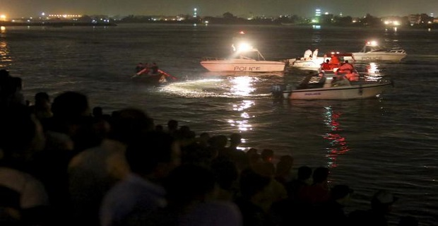 People gather along the banks of the Nile River during a search for the victims of a boat accident on the River Nile in the Warraq area of Giza