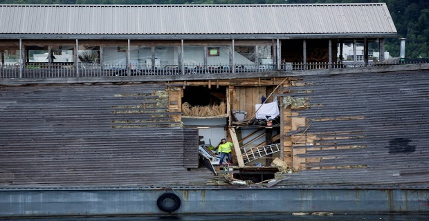 A crew member inspects damages on the hull of a full-size replica of the Ark of Noah after it crashed into a moored coast guard vessel in Oslo harbour