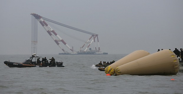 """Rescue workers operate near floats where the capsized passenger ship """"Sewol"""" sank, during the rescue operation as a giant offshore crane, which will take part in the rescue operation, is seen in the background in the sea off Jindo April 19, 2014. Divers searching for survivors of a capsized South Korean ferry saw three bodies floating through a window of a passenger cabin on Saturday but were unable to retrieve them, the coastguard said, hours after the ship's captain was arrested. REUTERS/Issei Kato (SOUTH KOREA - Tags: DISASTER MARITIME)"""